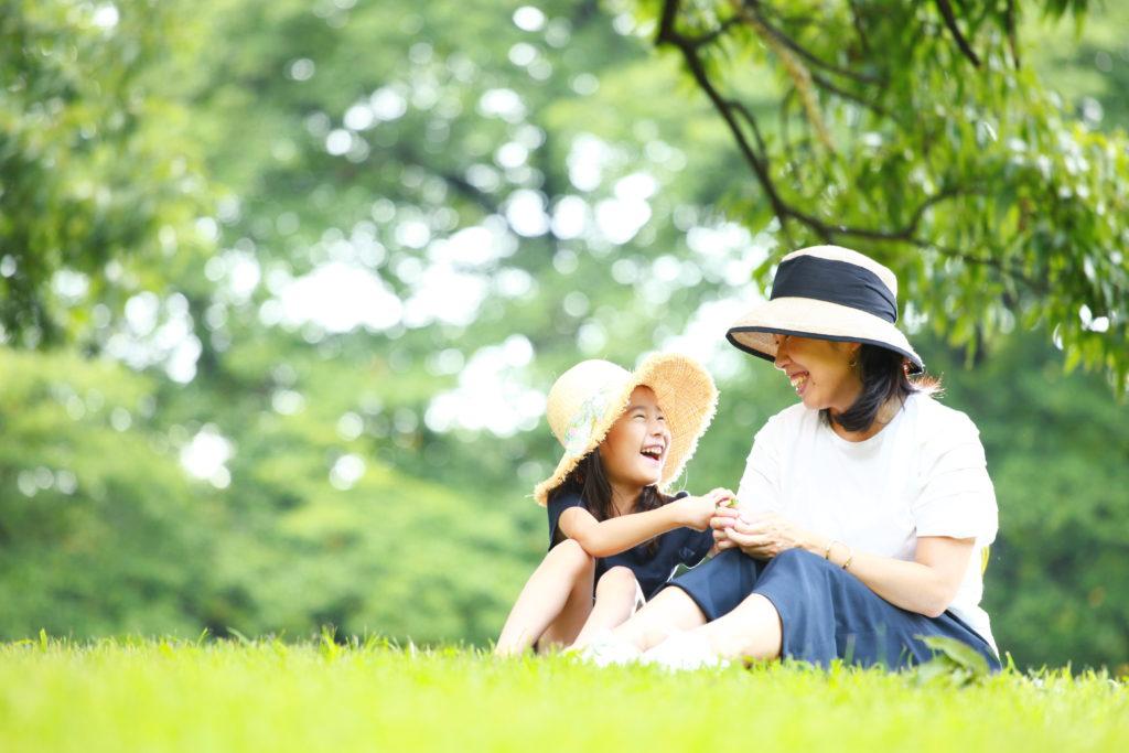 公園の芝生に座って楽しそうに会話をする親子