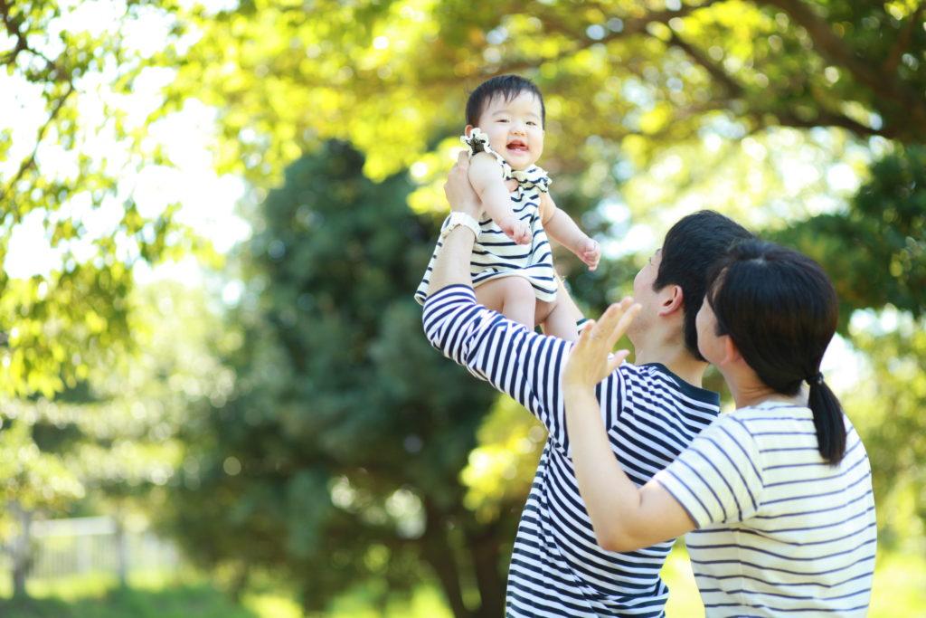 パパに抱っこされた笑顔の赤ちゃんとそれを見つめるママ