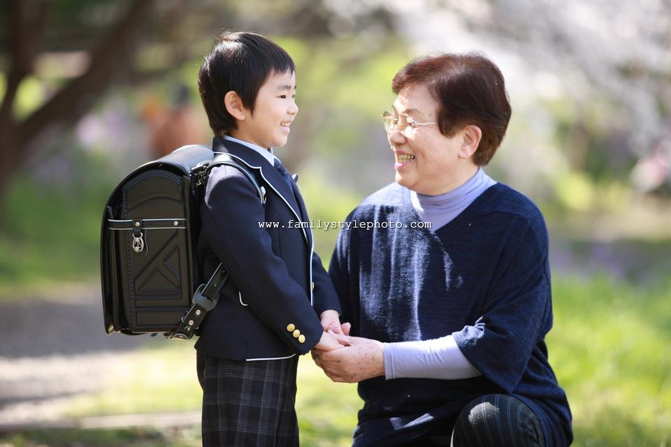 桜背景でおばあちゃんと一緒の男の子