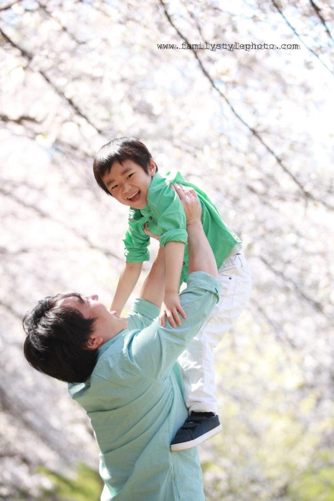 桜を背景にパパに高い高いされる子供