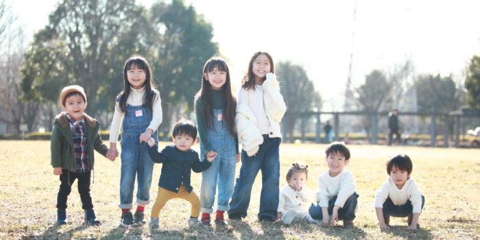 屋外でお友達と並んで写真撮影する子供たち