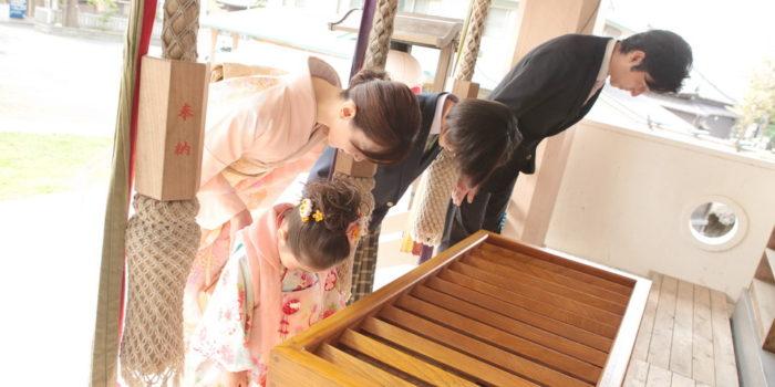 お賽銭箱の前で神様に挨拶をする家族