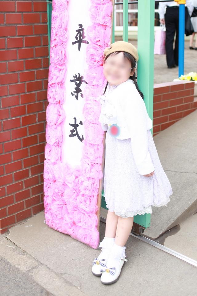 卒園式看板の前で写真を撮る子ども