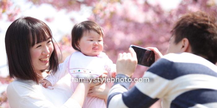 桜を背景にママと赤ちゃんの写真を撮るパパ