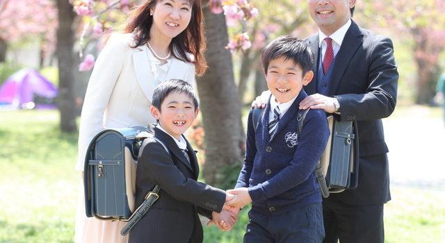 桜の下で入学記念の写真を撮る家族